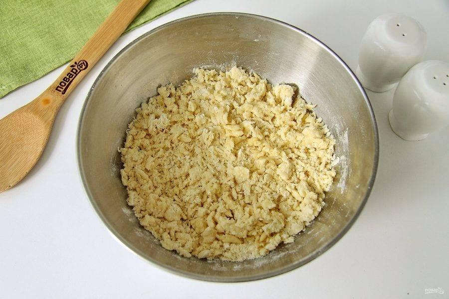 Муку соедините с теплым маслом и перемешайте до образования крошек.