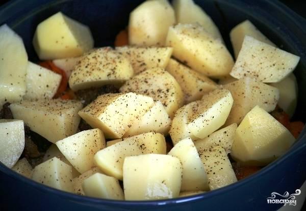 По истечению 40 минут запекания мяса, достаем форму для запекания из духовки, кладем в нее картофель, соль и перец. Аккуратненько перемешиваем.