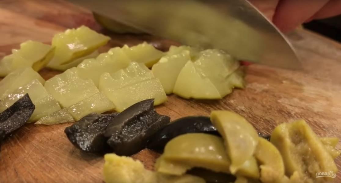 Нарезаем оливки продолговатыми кусочками (примерно на 6 частей каждую). Следом — огурцы, их нарезаем кубиками. Советую не мельчить.