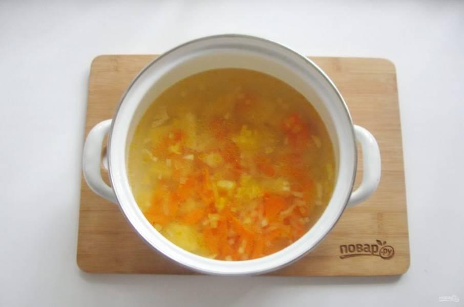 Лук и морковь выложите в кастрюлю с картофелем и бульоном. Продолжайте варить суп.