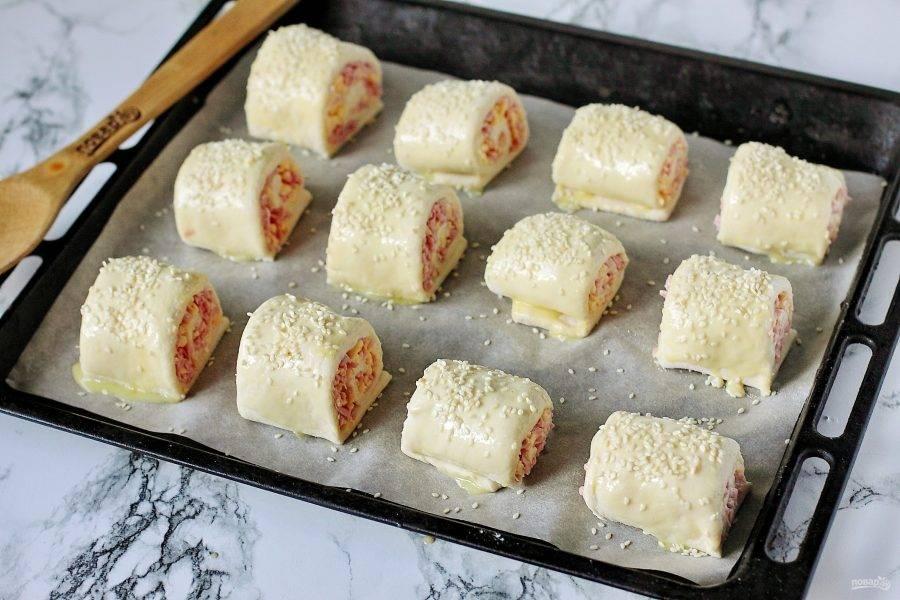Переложите рулетики на застеленный пергаментом противень. Смажьте яичным желтком (можно разбавить его молоком) и посыпьте кунжутом. Запекайте в духовке при температуре 180-200 градусов около 20 минут.