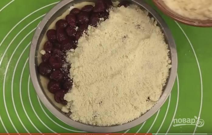 10. На вишню ложкой выкладываем приготовленную присыпку из муки, затягивая пирог до самого края.