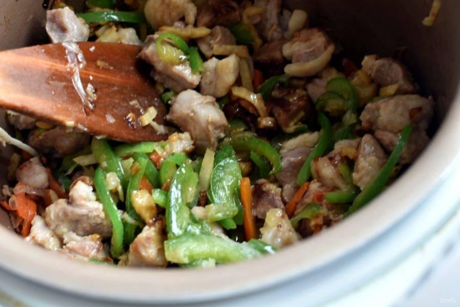 Добавьте нарезанный полосками сладкий перец и очищенные и разрезанные пополам дольки чеснока, жарьте еще 5 минут.