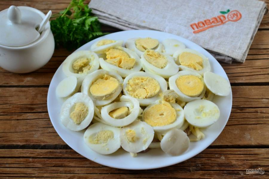 Выложите кружочки яйца и снова покройте майонезной сеточкой.