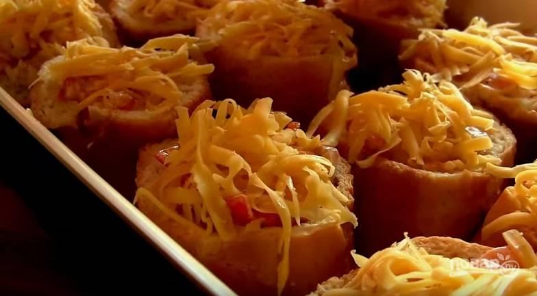 5. Форму для выпечки смажьте растительным маслом. Батон чуть отожмите и выложите в форму, сделайте углубления пальцами или ложкой. Выложите начинку, а сверху добавьте тертый сыр.