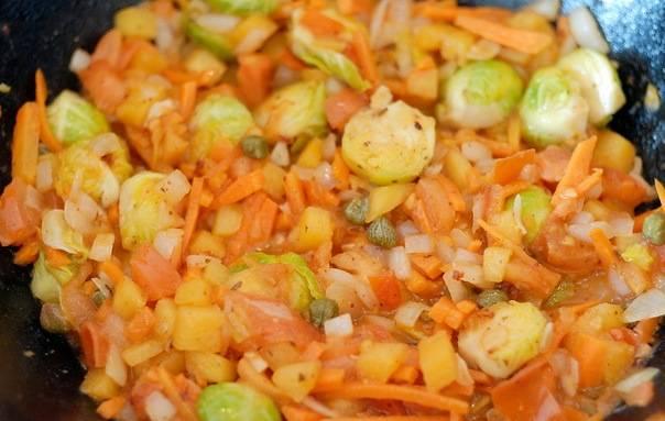 Чеснок раздавите и порубите. Разогрейте масло в воке или сотейнике, обжарьте чеснок, добавьте брюссельскую капусту, лук, морковь, тыкву и обжаривайте 3 минуты. Добавьте рубленые стрелки с фасолью, обжарьте ещё 2 минуты. Добавьте помидоры, каперсы, аджику и уксус. Потушите 2-3 минуты.