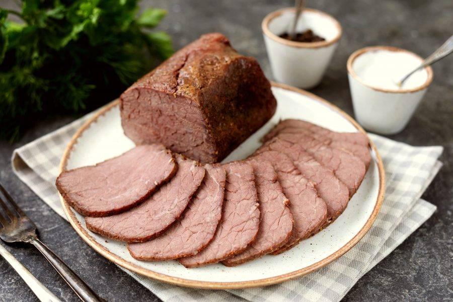 Спустя время извлеките мясо из духовки, проколите фольгу, слейте выделившийся сок. Остудите говядину прямо в фольге и в ней же отправьте в холодильник до полного остывания. Спустя несколько часов тоненько нарежьте буженину и подавайте в качестве холодной закуски.