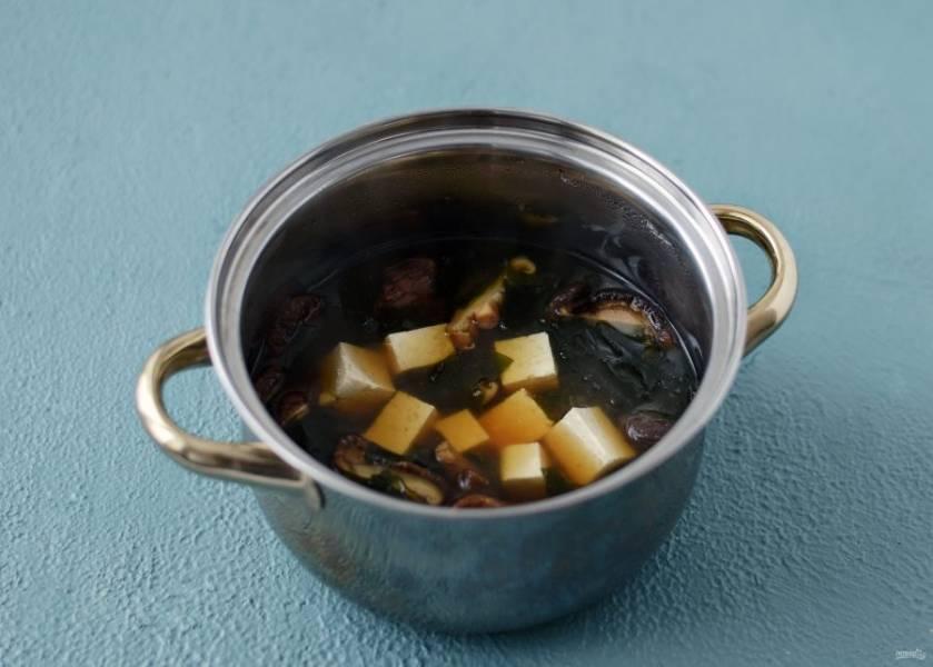 Налейте в кастрюлю воду, добавьте грибы с водой, в которой они замачивались. Варите шиитаке в воде 15 минут. Добавьте соевый соус и водоросли. В конце добавьте тофу и оставьте суп на пару минут настояться под крышкой.