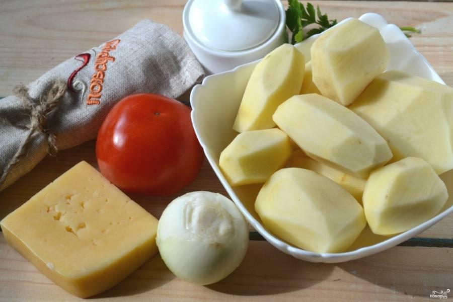 1.Подготовьте все необходимые ингредиенты. Картофель и лук очистите. Картофель порежьте на тонкие пластины. Луковицу и помидор порежьте четвертькольцами.