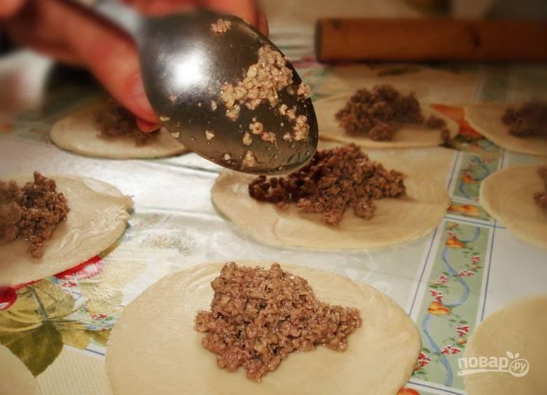 Слоеное тесто разморозьте, раскатайте в тонкий пласт. Разделите на небольшие круглые лепешки. В центр каждой выложите начинку.