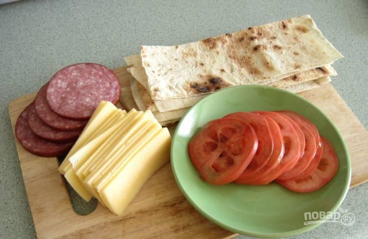 Нарезаем лаваш тонкими длинными полосками. Томат моем и нарезаем кружочками. Ломтиками нарезаем колбасу и сыр.