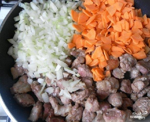 2. Помойте и очистите морковь, лук. Нарежьте морковку и лук на маленькие кусочки. Выложите в сковородку к обжаренной свинине. Перемешайте все компоненты. Продолжайте жарить на большом огне, периодически перемешивая, пока овощи не станут мягкими, приблизительно 2-3 минуты.
