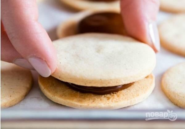 6. Выпекайте печенье до румяности около 15 минут, затем немного остудите его. На одну печенюшку выложите сгущенку, накройте второй.