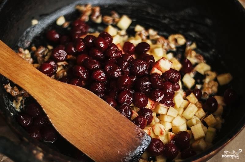 В сковороде разогрейте масло, нарубите орехи, добавьте их туда. Обжаривайте на огне, помешивая. Также добавьте вишню, яблоки, сахар и корицу. Всё перемешивайте и продолжайте готовить около 10 минут.
