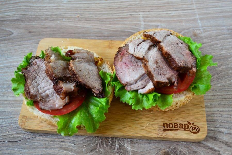 На салат положите по кружочку помидора (или несколько кружочков огурца или другие овощи). Чуть остывшее мясо порежьте на ломтики и положите сверху. Здесь мяса не жалейте, кладите по 2-3 больших ломтика.