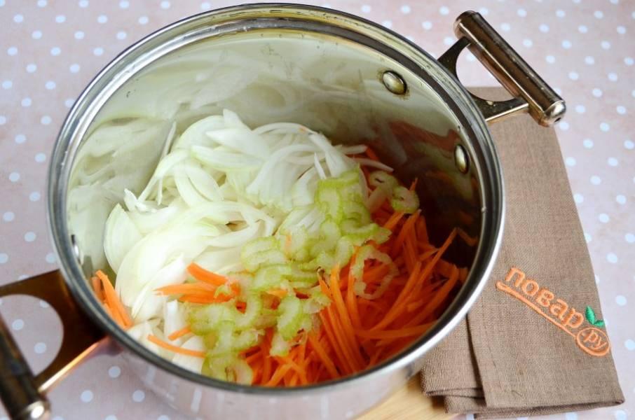 Сельдерей и лук тонко нарежьте полукольцами, морковь натрите на квадратной крупной терке. Обжарьте овощи в кастрюле на сливочном масле до мягкости.