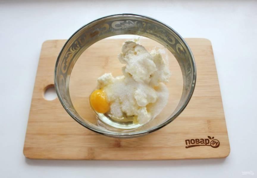 Выложите творог в миску. Добавьте яйцо и 40 грамм сахара.