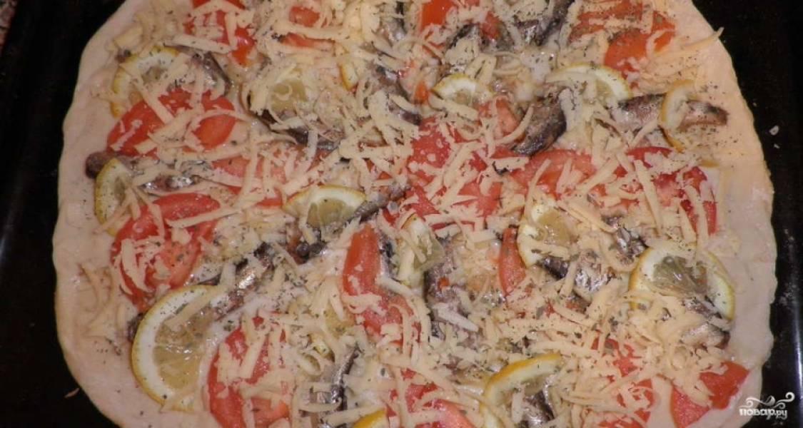 Раскатываем тесто, выкладываем на него шпорты с порезанными помидорами и лимоном. Кусочки должны быть тонкими. Посыпаем пиццу тертым сыром и базиликом.