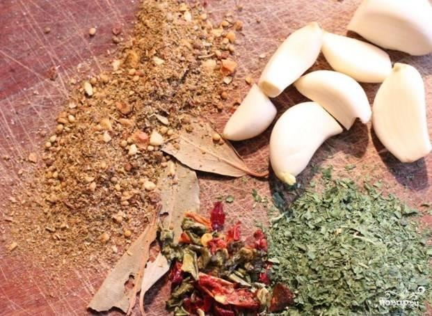 Чеснок почистите, зубчики порежьте на дольки. Мясо хорошенько посолите и поперчите, используйте специи для мясного жаркого.