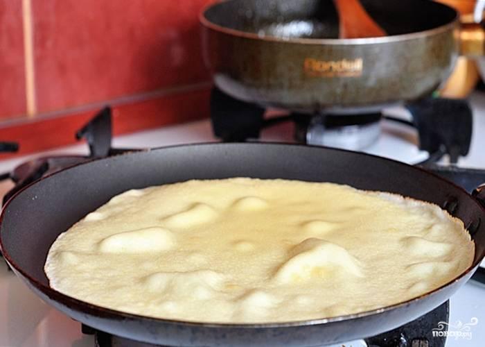 На разогретой с маслом сковороде выпекайте блины до готовности с двух сторон.