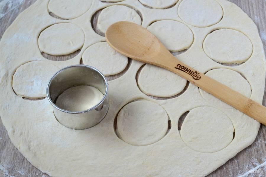 Снова обомните тесто, разделите его на 2 части. Одну часть раскатайте толщиной 3-4 мм, стаканом или специальной вырубкой выдавите кружочки диаметром примерно 7-8 см.
