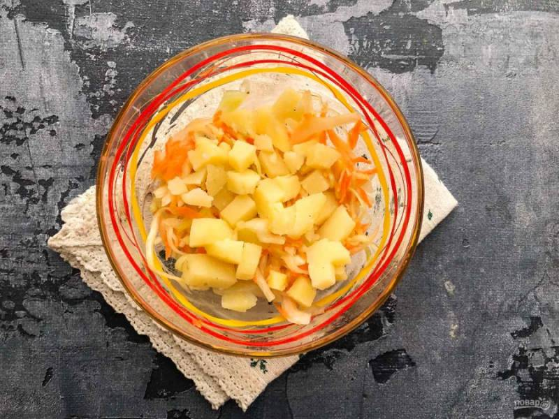 Вареный картофель очистите от кожуры, нарежьте небольшими кубиками и добавьте к капусте.