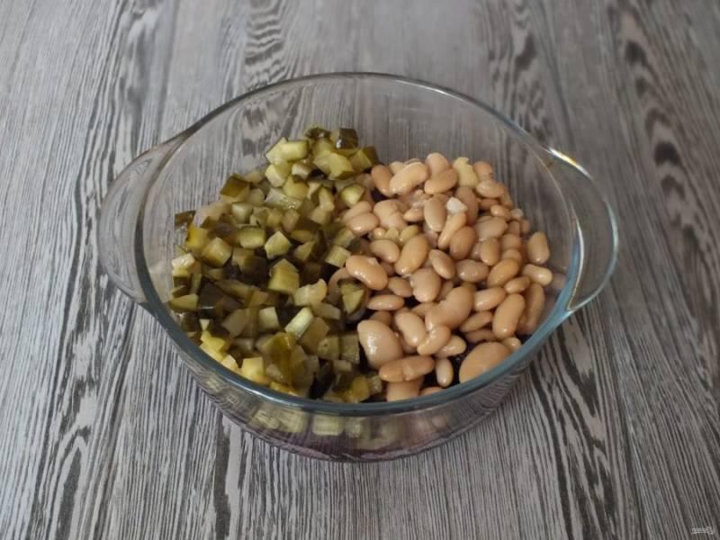Добавьте к свекле нарезанные средним кубиком огурцы и фасоль. С консервированной фасоли предварительно слейте жидкость.