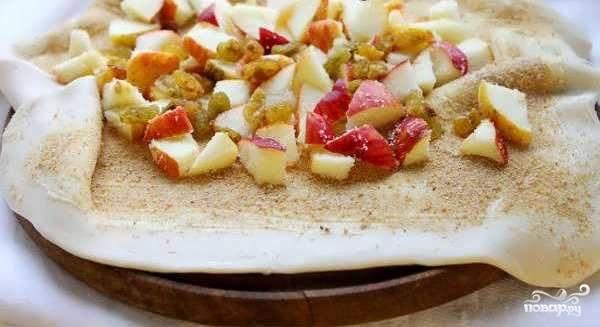 Яблоки и изюм выложите на тесто. Равномерно распределите начинку по всему пласту теста так, чтоб по бокам осталось два-три сантиметра пустоты, чтобы было удобно заворачивать штрудель рулетиком.