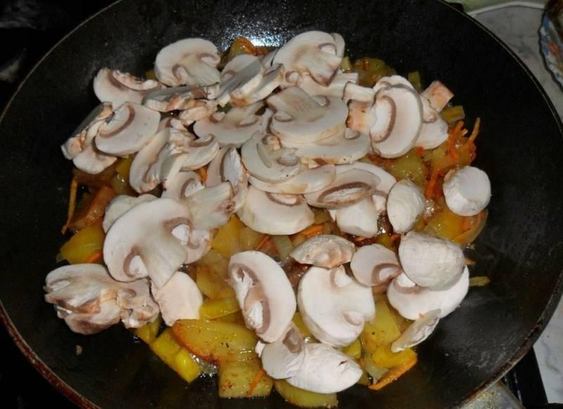 Пока жарятся овощи, мы тщательно промываем грибы и нарезаем их на пластинки, затем кладем шампиньоны к остальным ингредиентам, жарим все еще 5-7 минут.