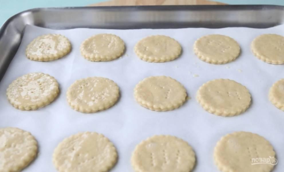 4.Раскатайте тесто в пласт толщиной полсантиметра и вырежьте кружочки. Наколите коржики вилкой и смажьте взбитым яйцом. Выпекайте при температуре 180 градусов 15-20 минут или до золотистого цвета.