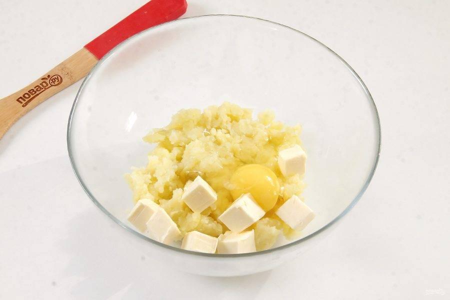 Для теста соедините в глубокой миске картофельное пюре, нарезанное кусочками сливочное масло и одно яйцо.