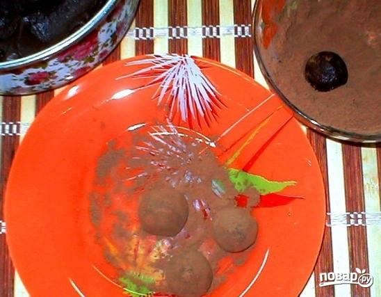 """Теперь вам необходимо сформировать из шоколодного """"пластилина"""" шарики или же любые другие фигуры, напоминающие по форме конфеты. Каждую из них обмакните в какао. Готовые конфеты выложите на бумажки и поставьте застыть в холодильник на час."""