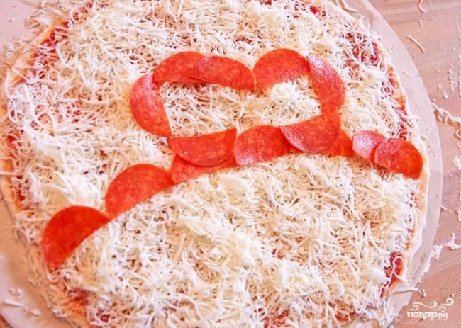 4. Половину кружочков салями нарежьте напополам. По центру пиццы выложите полукруг из обрезанных кусочков колбасы срезом вниз, чтобы получилась дуга. Затем в центре на дугой сформируйте обрамленный прямоугольник из половинок салями.