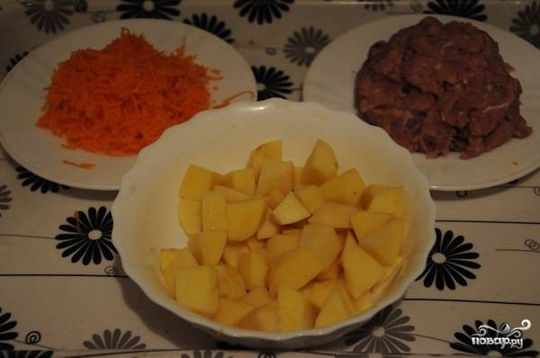 2. Нарежьте небольшими кусочками картофель. Морковь натрите на терке. Половину лука измельчите кубиками, остальную часть оставьте для фарша. Пропустите мясо через мясорубку вместе с луком и чесноком. Затем посолите и поперчите по вкусу, все как следует перемешайте. Когда вода закипит, добавьте в кастрюлю щепотку соли и выложите картофель.
