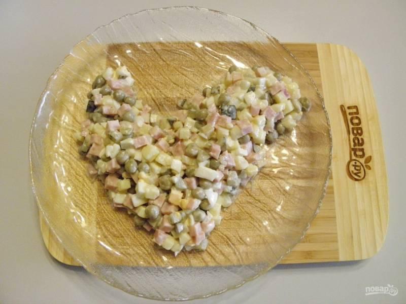 Возьмите большое плоское блюдо и выложите салат, придавая форму петушка.