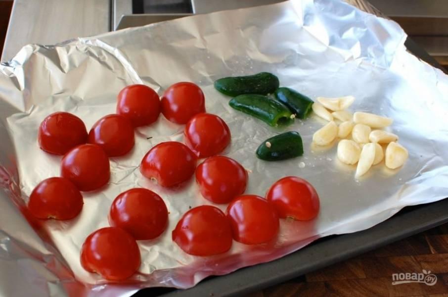 2.Помойте помидоры и разрежьте пополам, почистите чеснок. Выложите помидоры, перец халапеньо срезом вниз на противень, застеленный фольгой, туда же положите чеснок.