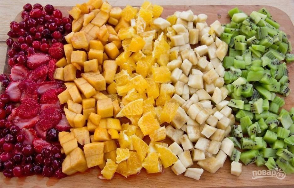 Промойте, очистите и нарежьте фрукты и ягоды кусочками приблизительно одинакового размера.