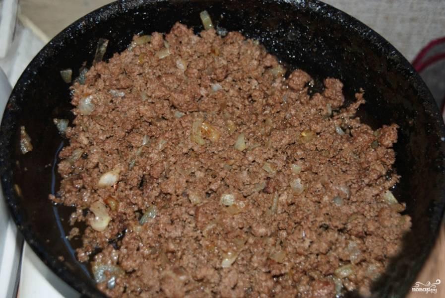 Фарш выложите в сковороду и начинайте обжаривать на растительном масле. Репчатый лук очистите и мелко нарежьте. Лук добавьте в сковороду и обжарьте вместе с фаршем.