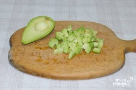 Авокадо очистите от кожуры и удалите косточку, а затем нарежьте плод небольшими кубиками.