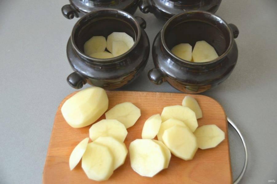 Картофель порежьте кружочками, выложите на дно горшочков.