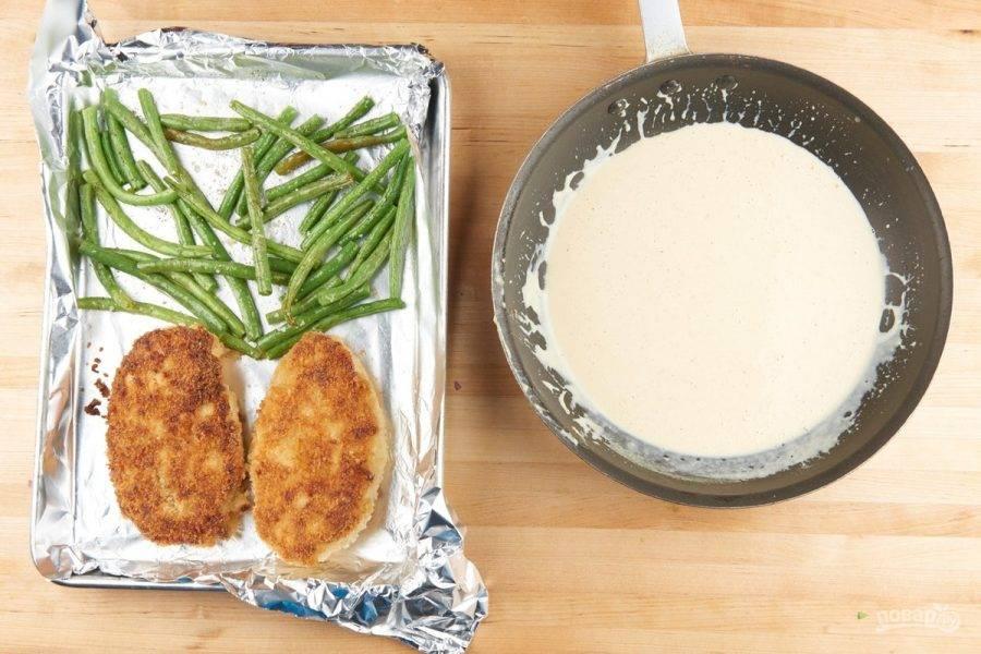 5. Далее на противень также выложите фасоль. Предварительно посолите её и поперчите. Запекайте ингредиенты 11 минут при 200 градусах в духовке. Сделайте соус, подогрев в сотейнике пару минут сметану с горчицей.