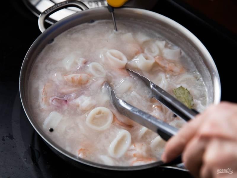 Кальмара режем кольцами, измельчаем осьминога. Достаем мидии и в эту же воду кладем осьминога, креветки и кальмаров. Варим в кипящей воде минуты 3. По желанию можете добавить лавровый лист и перец-горошек.