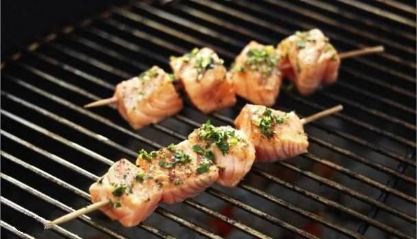 Деревянные шпажки смачиваем в воде и нанизываем на них рыбу. Выкладываем шашлык на решетку, установленную на мангал. Готовим примерно по 1-2 минуты с каждой стороны, чтобы рыба не подгорела. Приятного аппетита!