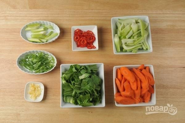 1. Подготовьте все овощи. Пропустите через пресс чеснок. Перец нашинкуйте тонкими кольцами. Морковь нарежьте под углом. Зелёную часть лука нашинкуйте кольцами, отдельно крупно нарежьте белую часть. Пак-чой разделите на несколько частей.