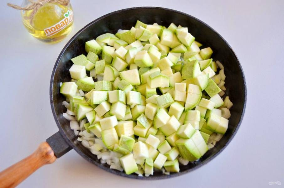 2. Порежьте мелко лук, обжарьте пару минут на растительном масле. Молоденькие кабачки порежьте кубиками, если кожура жесткая, то очистите ее. Добавьте к луку, жарьте 10 минут, посолите.
