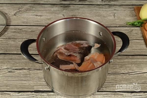 2. Для начала нужно поставить варить бульон. Голову (+хвост, хребет и т.д.) вымойте, выложите в кастрюлю и залейте водой. Поставьте на огонь. После закипания варите на медленном огне около 20 минут.