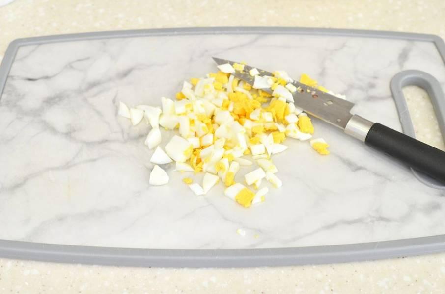 Яйца отварите, охладите, измельчите.