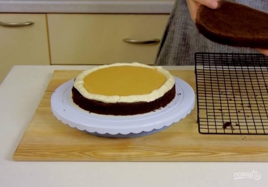 5. Часть крема переложите в кондитерский мешок и сформируйте валик по краю первого коржа. Распределите карамельный соус в середине валика и накройте вторым коржом. Верх и бока торта смажьте кремом.