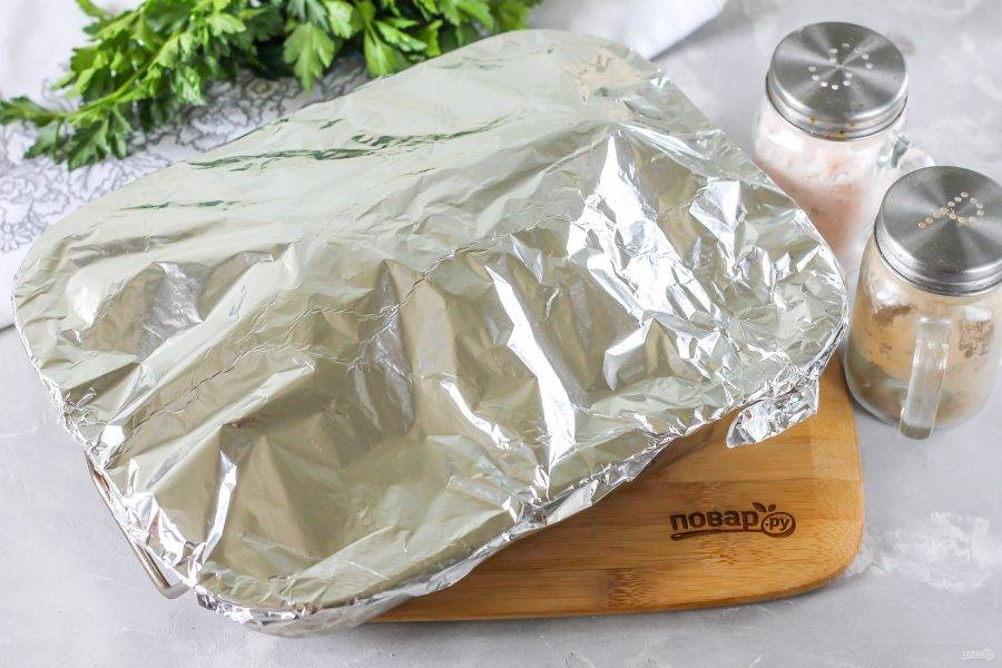 Накройте противень сверху фольгой и тщательно ее запечатайте. Разогрейте духовку до 200 градусов и поместите в нее противень с рулькой на 1,5-2 часа.