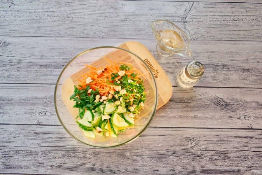 Орехи обжарьте на сухой сковороде до румяной корочки, подробите. Огурцы нарежьте крупными полукольцами, слегка прижмите, чтобы удалить как можно больше жидкости. Морковь натрите на корейской терке. Кинзу измельчите, зеленый лук нарежьте крупными кусками.